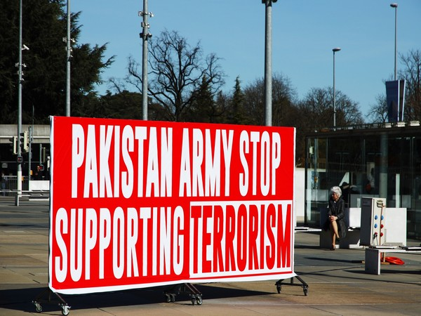 A banner reading 'Pakistan Army Stop Supporting Terrorism' displayed outside UNHRC headquarters in Geneva.