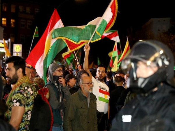 Kurdish protesters waving a flag during a demonstration against Turkey's military action in northeastern Syria, in Berlin, Germany on Saturday. (Reuters)