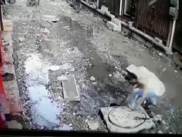 Visuals of a man rescuing a child from a gutter n Jodhpur. (Photo/ANI)