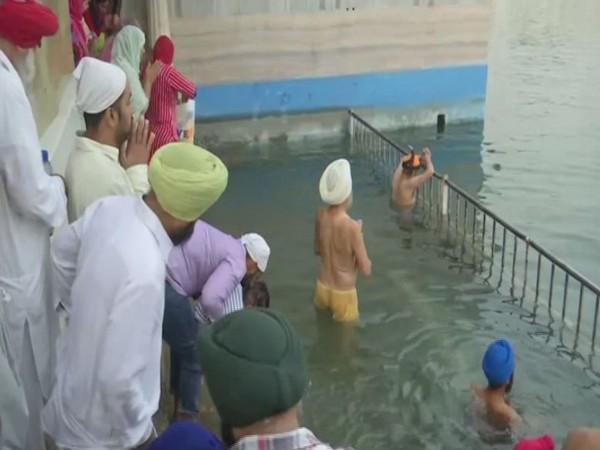 Sikhs taking a holy dip in Golden temple in Amritsar [Photo/ANI]