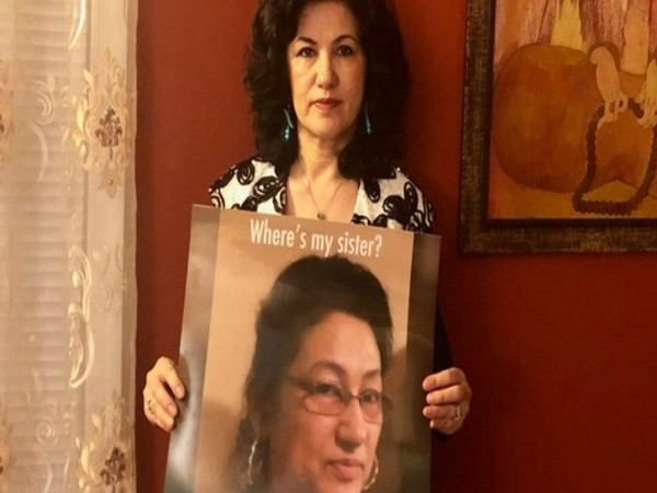 Activist Rushan Abbas with a poster of her sister, Gulshan Abbas.