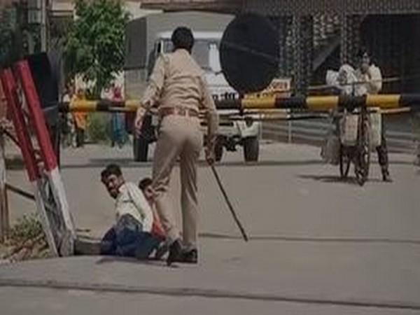 Police make labourers roll on road in Hapur on Tuesday. Photo/ANI