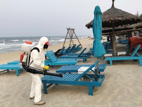 A health worker sprays disinfectants to protect against the coronavirus on a beach in Hoi An