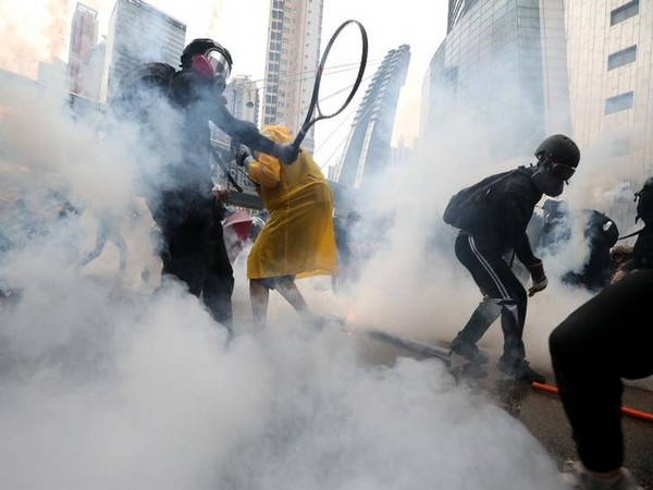 Demonstrators react to tear gas as they clash with riot police during a protest in Hong Kong