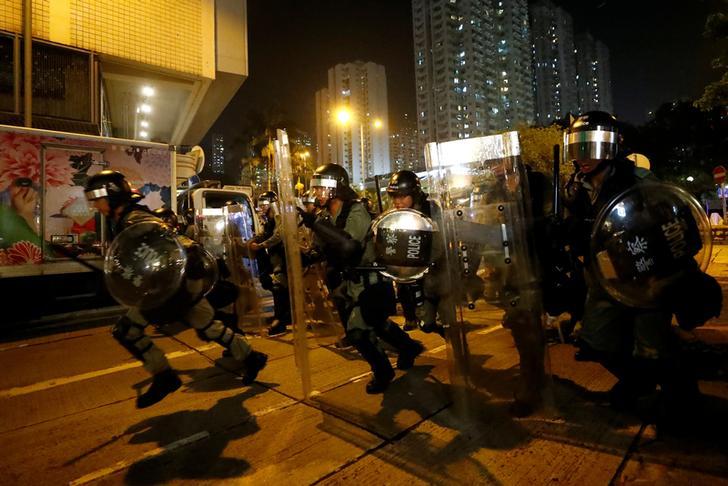 Riot police chase demonstrators during a protest in Hong Kong