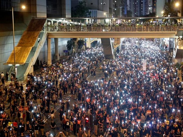 Protesters use flashlights of mobile phone during the march on July 1