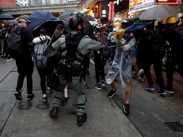 A riot police officer clashes with a protester during an anti-government rally in central Hong Kong on Sunday
