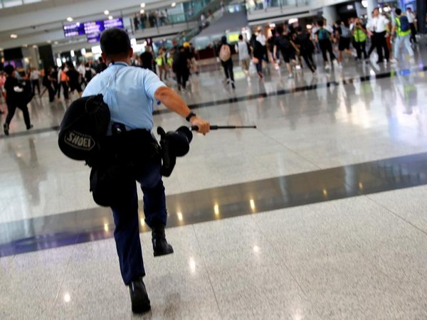 An earlier instance of a police officer chasing mob at the Hong Kong International Airport.