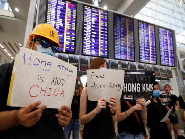 Protestors holding signs in English and Chinese at the Hong Kong International Airport to explain the cause and demands of their demonstrations.
