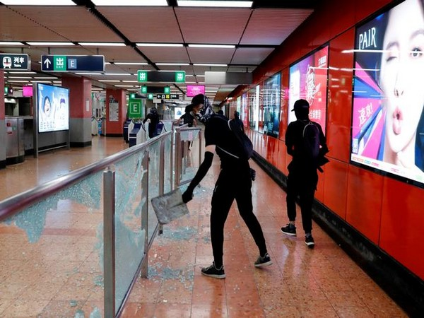Anti-government protesters wearing mask smash Mong Kok Mass Transit Railway (MTR) station during a demonstration on Friday.