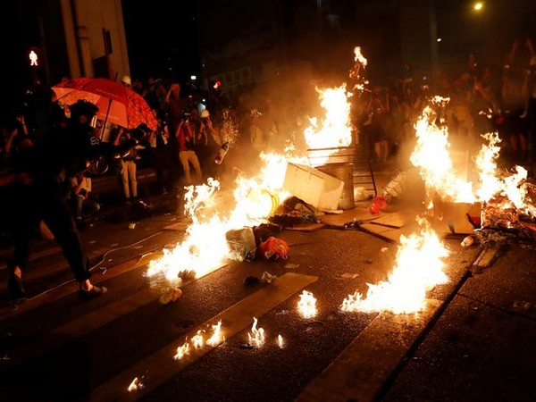 An anti-government protester sets fire during a rally outside Mong Kok police station, in Hong Kong