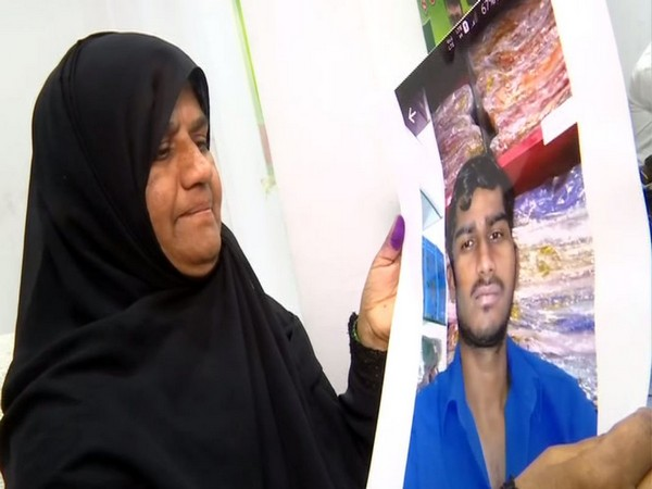 A mother in Hyderabad holding photo of his son stranded in Bangladesh.