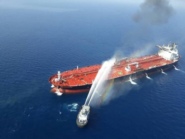 An Iranian navy boat tries to stop the fire of an oil tanker after it was attacked in the Gulf of Oman on June 13