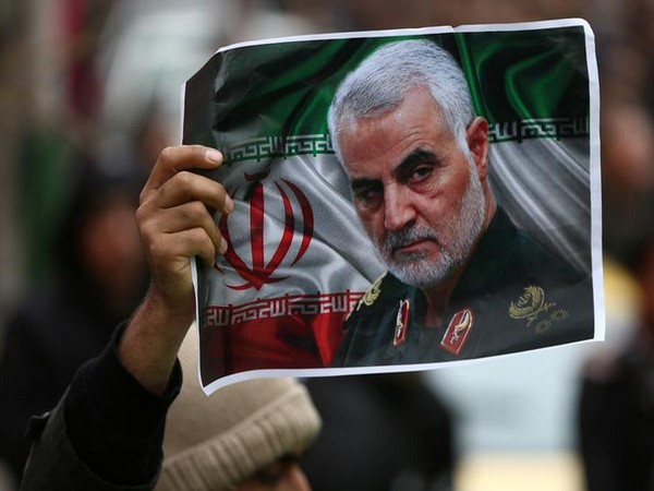 An Iranian holds a picture of late General Qassem Soleimani