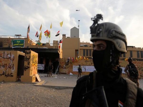 Members of Iraqi security forces in front of US Embassy during a protest to condemn airstrikes on facilities linked to Iranian-backed Kataib Hezbollah militia in Iraq and Syria.