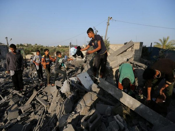 Palestinians collect belongings from a house destroyed in an Israeli air strike in the southern Gaza Strip on Thursday