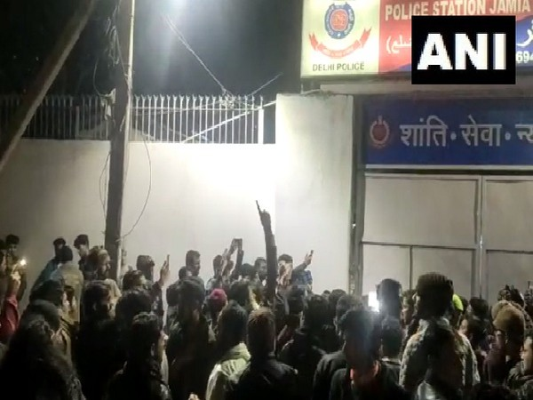 People gather outside Jamia Nagar police station in New Delhi following firing near the university.