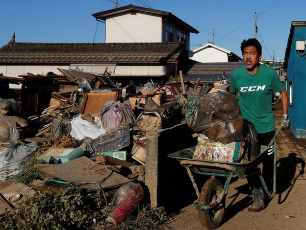 A man cleans debris in the aftermath of Typhoon Hagibis in Yanagawamachi district on Wednesday (Photo/Reuters)
