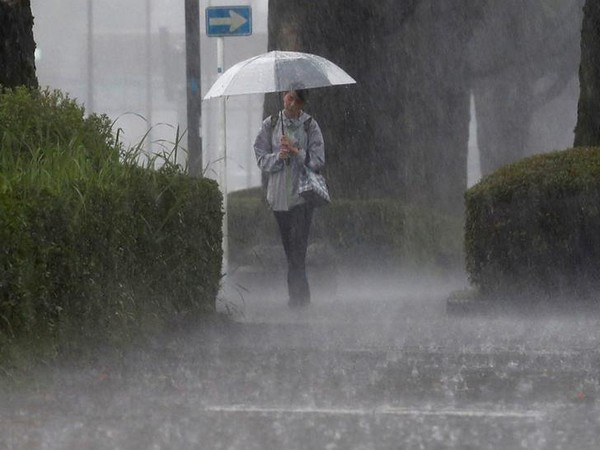 A pedestrian walks through the heavy rain in Kagoshima (Photo/Reuters)
