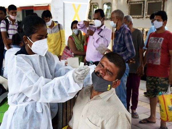 A healthcare worker collecting the swab sample of a man for COVID-19 testing. (Photo/ANI)