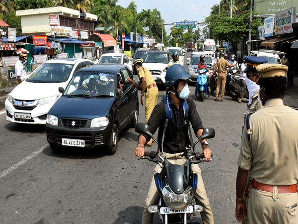 Police personnel stop commuters during lockdown in Kochi on Tuesday. (ANI Photo)