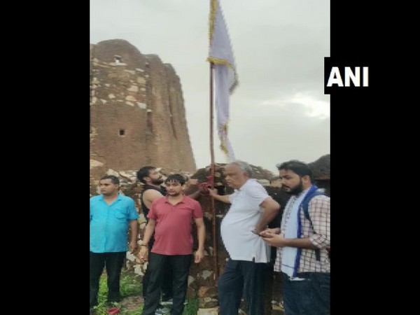 Kirodi Lal Meena standing with the flag at Amagarh Fort in Jaipur, Rajasthan.