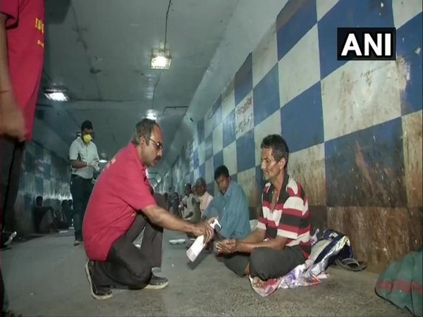 ocial workers distributed food to destitute people who have taken shelter at underpass of Dum Dum railway station [Photo/ANI]