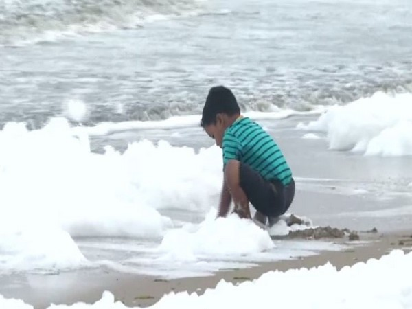 A child playing in the white foam formed at the surface of Marina beach in Chennai on Monday. Photo/ANI