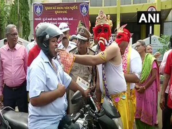 Traffic police offering laddus to bike riders wearing helmet at Rajkot
