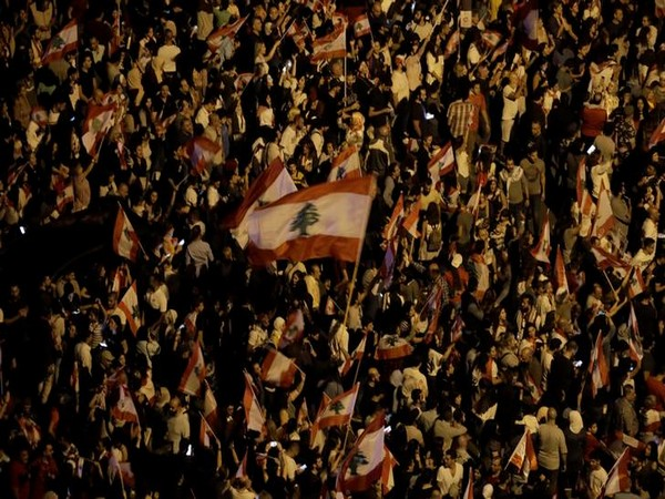 Demonstrators hold Lebanese flags during anti-government protests in Beirut on Sunday evening. Photo/Reuters