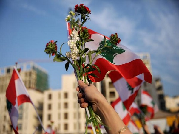 A woman marches holding a Lebanese flag and flowers during a parade, on the 76th anniversary of Lebanon's independence, at Martyrs' Square in Beirut.