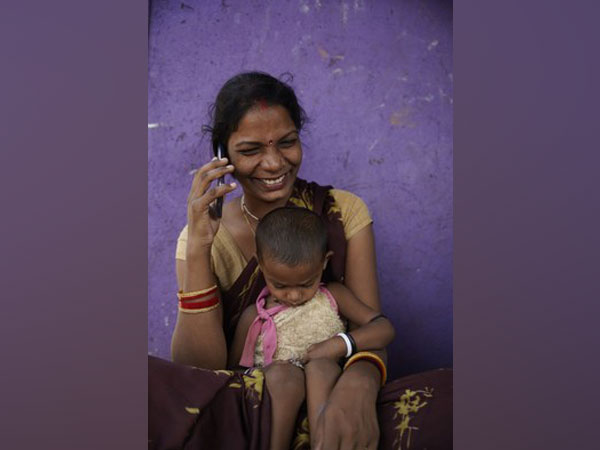 A woman listens to an mMitra calls on her phone in Nala Sopara, Mumbai
