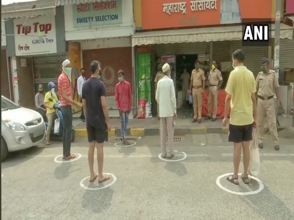 People standing in separate circles marked with chalk while collecting basic supplies from a grocery shop at Andheri East on Wednesday. Photo/ANI