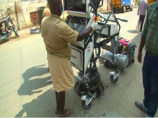 A Coimbatore municipal corporation worker uses robot to clean clogged drains [Photo/ANI]