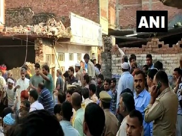 Locals gather at the spot where a house collapsed following a cylinder blast in Mau, Uttar Pradesh on Monday