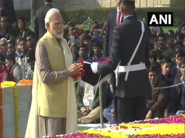 Prime Minister Narendra Modi offers floral tributes to Mahatma Gandhi at Raj Ghat in New Delhi.