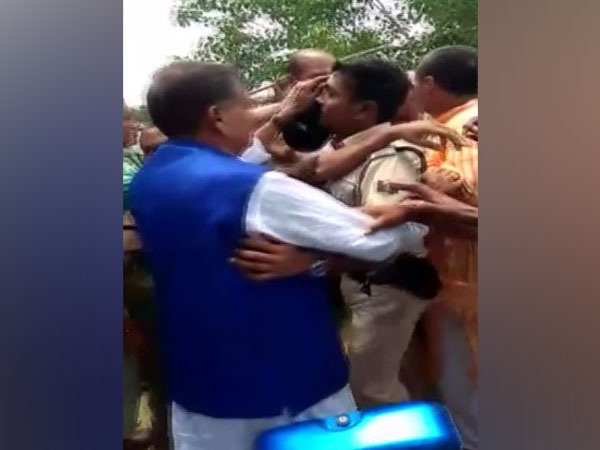JD (U) MP from Jhanjharpur constituency, RP Mandal being protected by police in a villager in Bihar.