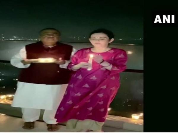 Mukesh Ambani with his wife Nita Ambani lights candle in Mumbai on Sunday. Photo/ANI