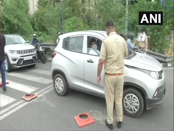 Police personnel checking IDs of commuters near Noida-Delhi border.