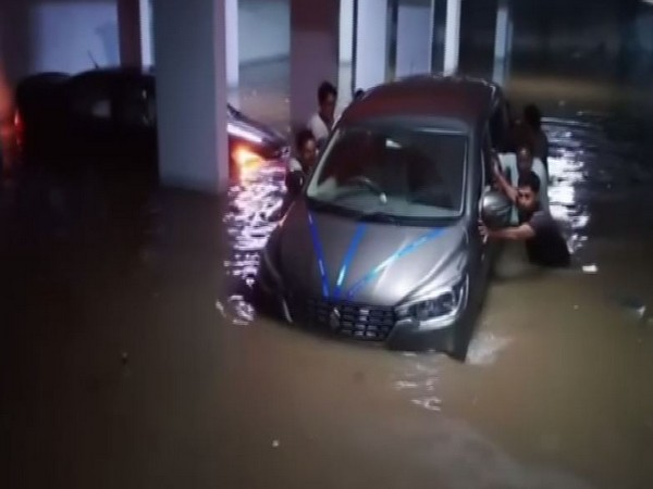 People moving their vehicle from the waterlogged parking lot of some area in Hyderabad after heavy rains lashed the area on Thursday. Photo/ANI
