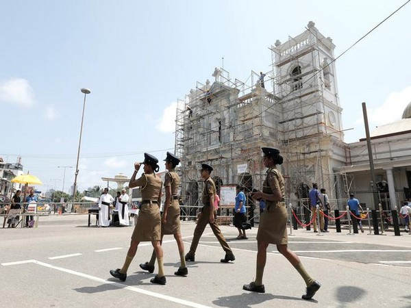 Sri Lankan police officers walk near the St. Anthony church, which was severely damaged in the Sri Lanka serial blasts last month
