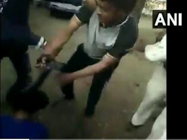 A grab of the video where Gandhwani Police Station Incharge Narendra Suryavanshi is assaulting his wife in Dhar district on Tuesday [Photo/ANI]