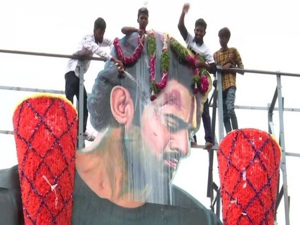 Fans of Prabhas pouring milk on his cutout in Hyderabad