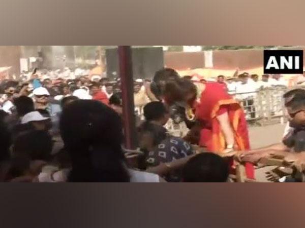 Congress general secretary Priyanka Gandhi climbs over a barricade in Ratlam