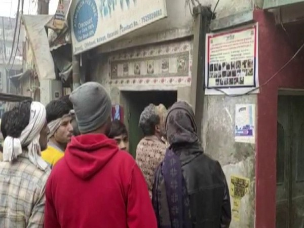 Locals in Varanasi carefully looking at the poster having the photographs of protsters who fanned violence on December 20 [Photo/ANI]