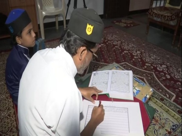 Mohammed Afzal copies the Quran in his handwriting. (Photo/ANI)I