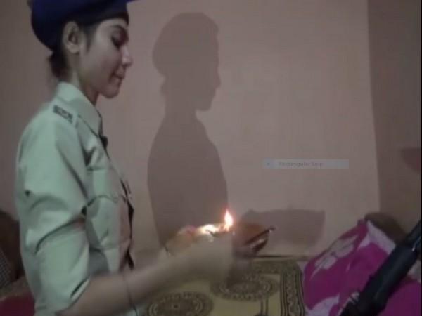 Kavita Kaushal ties a rakhi to her brother's rifle in Dantewada. Photo/ANI