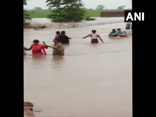 locals helps rescue few stranded people at a flooded bridge in Sagar District