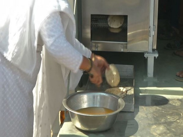 Fresh rotis being baked in the machine to be served to the hungry. (Photo/ANI)