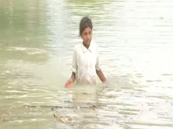 A girl moving through the flood in Bihar's Samastipur